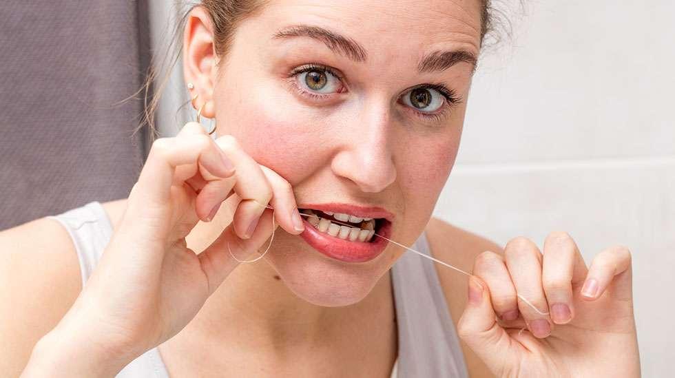 Nainen käyttää hammaslankaa