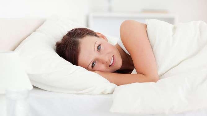 Nainen sängyssä. Kuva: Crestock
