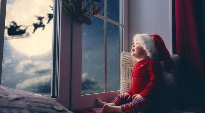 Vauva katsoo taivaalla lentävää joulupukkia ja poroja.