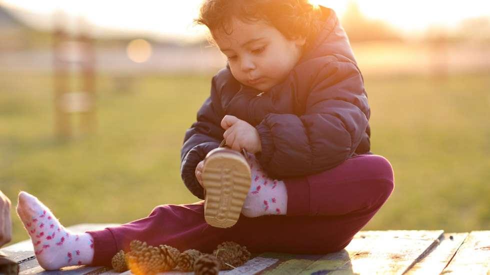 Lapsi osaa jo pukea ainakin osan vaatteistaan. Kenkien pukeminen voi olla vielä haastavaa. Kuva: iStock