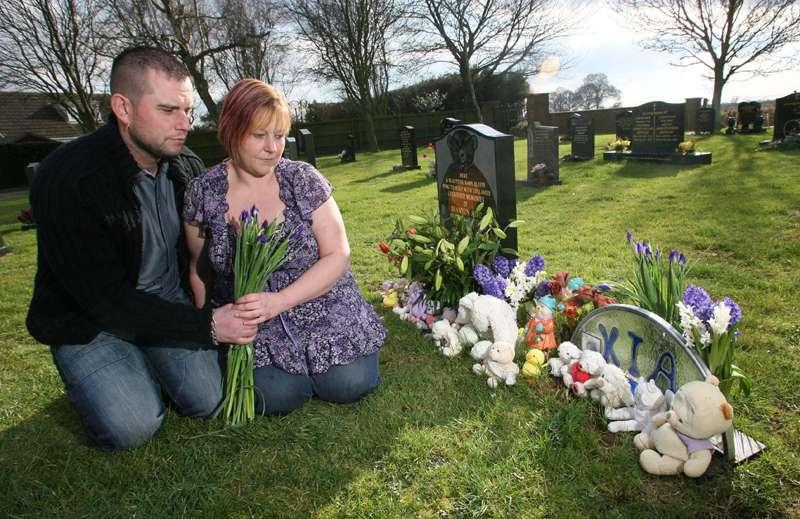 Maria ja John lastensa Kian ja Shannonin haudalla.