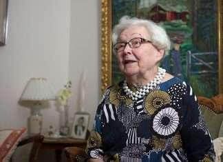 Iloinen ikänainen Helvi Husso kertoo lapsuusajan muistoistaan haastattelutilanteessa.
