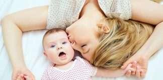 nainen makaa sängyllä vauvan vieressä ja antaa pusun
