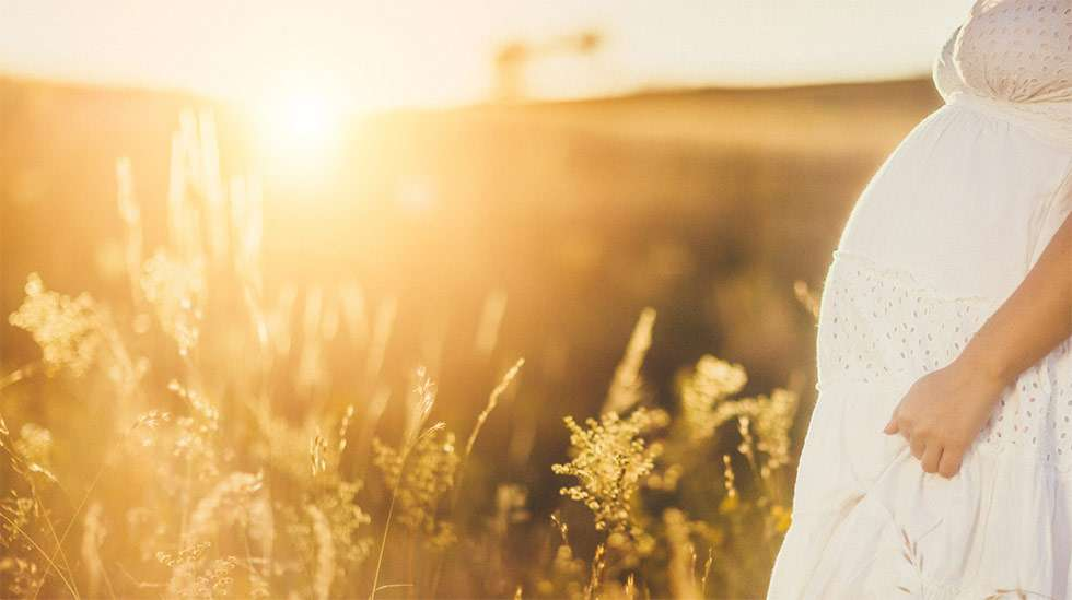 Nainen pellolla raskaana.