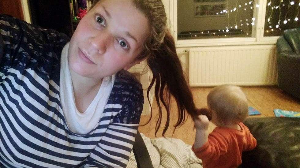 Moderni Tähkäpää-tarina: Taapero roikkuu äitinsä hiuksissa tämän suorittaessa etäopintojaan.