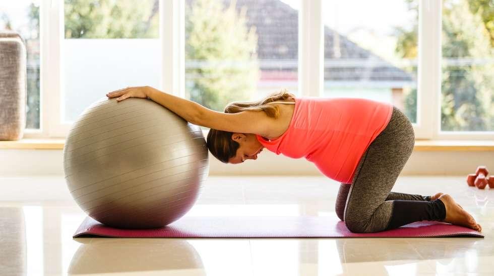 Voit rentoutua esimerkiksi asettumalla konttausasentoon lattialle jumppapalloa tai sohvaa vasten. Näin vauva pääsee riippukeinuun kohtuasi vasten. Kuva: iStock