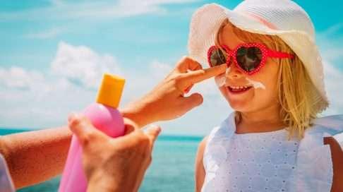 Erityisesti pikkulapset tulee suojata auringolta ensisijaisesti vaatteilla. Esiin jäävät ihoalueet suojataan aurinkovoiteella, jota tulisi lisätä noin kerran tunnissa. Kuva: iStock