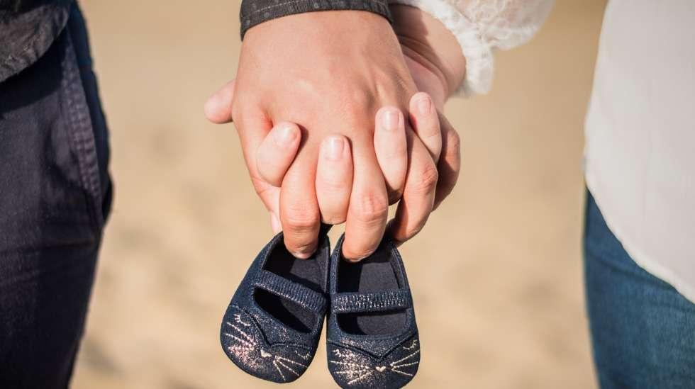 Valokuva pariskunnan käsistä ja pienet kengät – selkeä ja suloinen viesti siitä, että odotatte vauvaa! Kuva: iStock