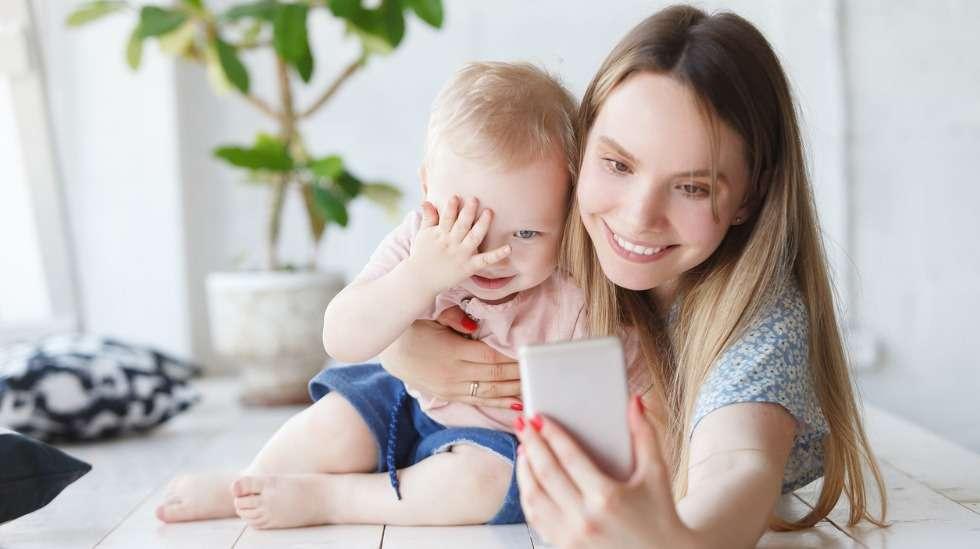 Laskeudu puhelimen kanssa lapsen tasolle, sanoita lapselle mitä puhelun aikana tapahtuu ja hyväksy se, että lapsi poistuu välillä touhuilemaan omiaan. Kuva: iStock